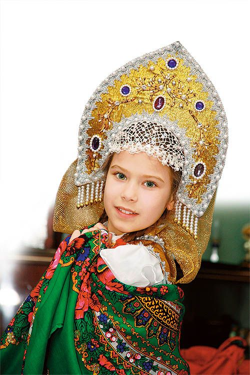 """A Russian girl in national outfit: headdress """"kokoshnik"""" and traditional shawl."""