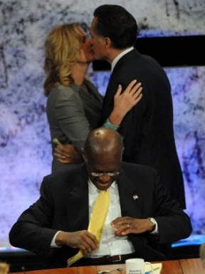 Mitt and Ann Romney kissing in front of a sitting Herman Cain. Who photobombed who here?