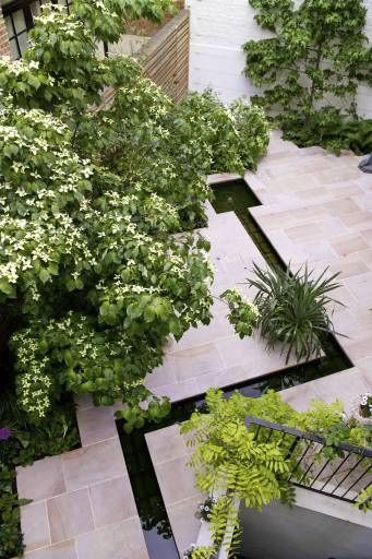 Large Slate Tiles and a unique water feature make a statement on this patio.  Found on http://www.fennelandfern.co.uk gardening blog.