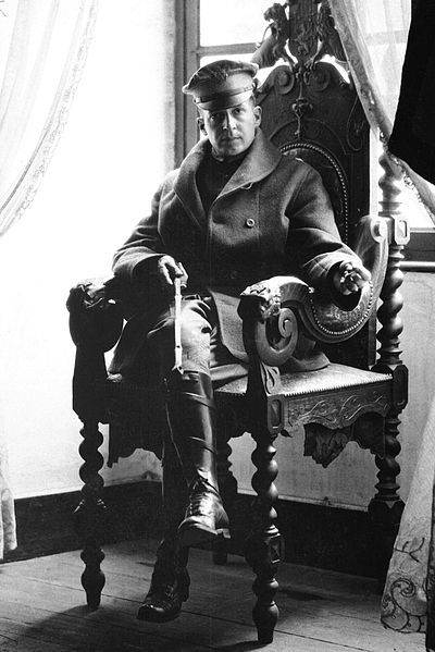 """World War I: Brigadier General Douglas MacArthur, already displaying his knack for public relations snapshots, poses with a riding whip seating on an imperial armchair at a French chateau in 1918. Note that the fact MacArthur could not touch the floor with his feet because of the size of the throne did not stop him from having the photo taken because he apparently appreciated the undisputed """"imperial"""" moment as part of his pictorial record."""