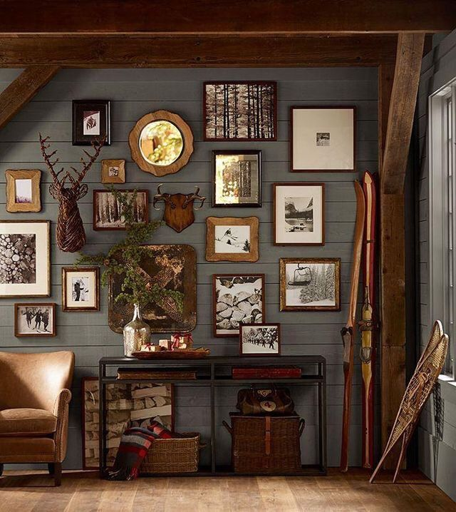 Lodge Decor -- hunter green walls, gallery frames, wooden skiis, leather  chair, faux deer antlers