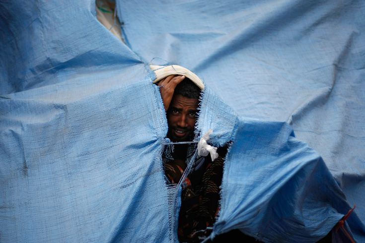 An Eritrean asylum seeker looks through a gap of a temporary shelter on the sidewalk in Sanaa, Yemen, June 20. Since April 29, over 200 Erit...