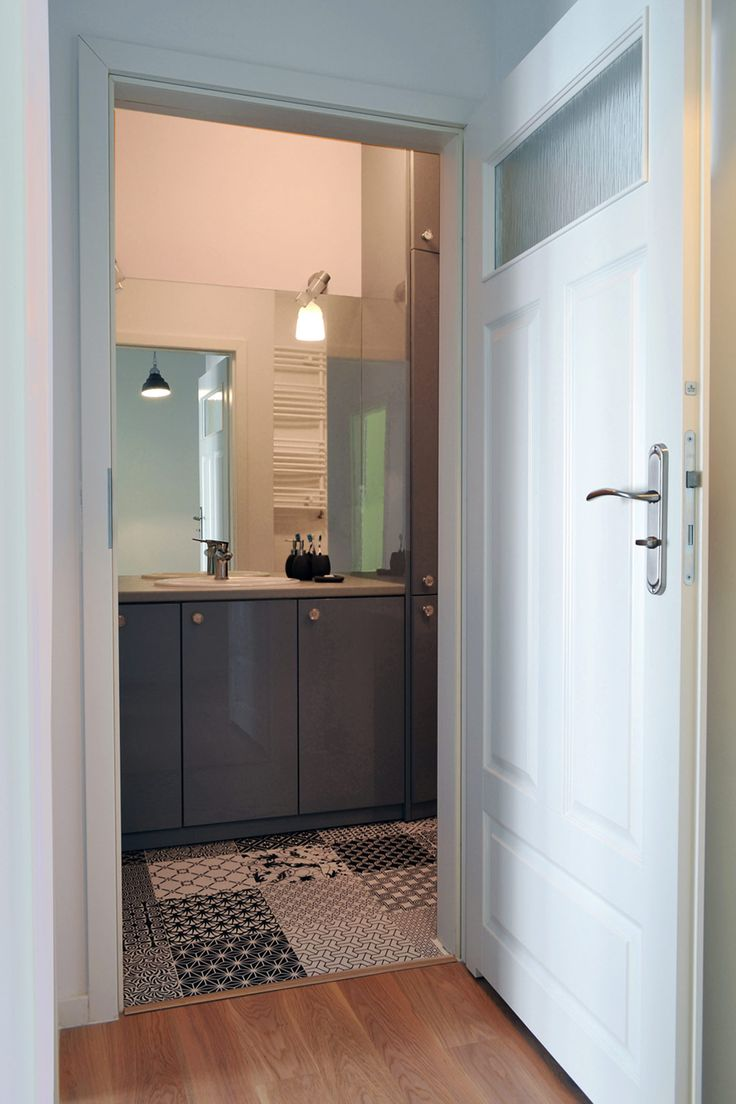 Szafka łazienkowa w szarym kolorze + czarno-białe płytki w stylu marokańskim. Białe, klasyczne drzwi nawiązują do stylu skandynawskiego.