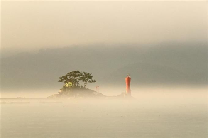 """大槌湾に浮かぶ蓬莱島。2つの丘からなる姿は""""ひょうたん島""""そっくりだ。再建された灯台は町民がデザイン。復興を目指す町の明るい未来を太陽と砂時計で表現した =岩手県大槌町(古厩正樹撮影)"""