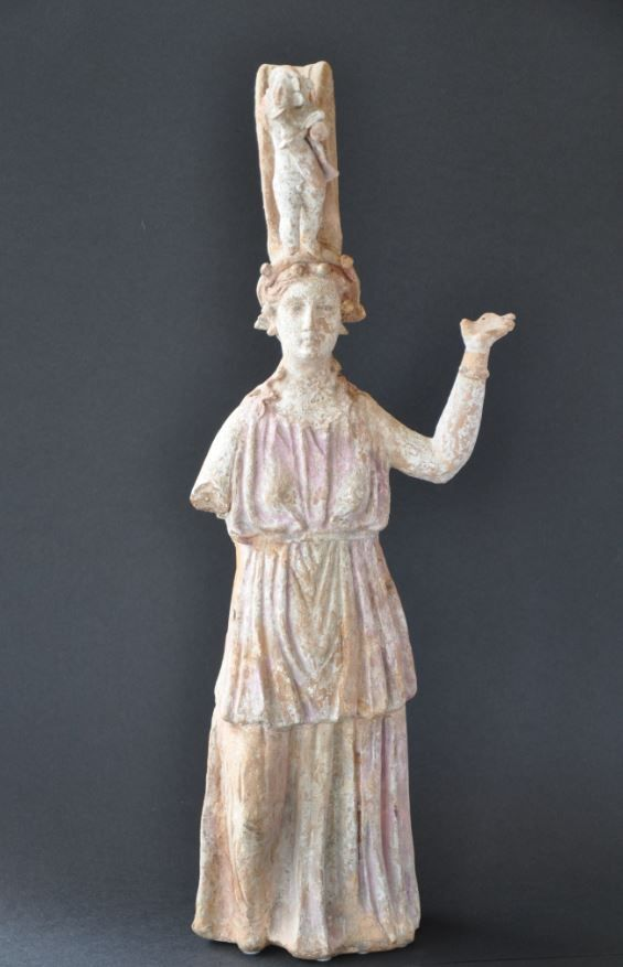 Greek terracotta statuette Canosan terracotta statuette, 4th century B.C. Greek terracotta figure, Canosan pottery statuette wearing tunic with raised arms, handle with applied statuette of Erotes holding amphora, remains of pink and blue decoration, unpublished type, 52.5 cm high. Private collection