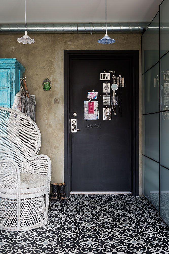 Pintada com uma tinta magnética de quadro negro, a porta principal serve de quadro de avisos. O charme final fica por conta das duas graças de luminárias e o belo tapete marroquino.