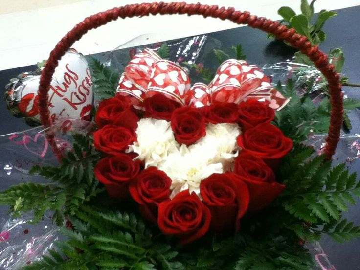 Dozen red roses in a basket with 3 white carnations and bakers fern in the shape of a heart. Perfect arrangement for Valentine's Day.