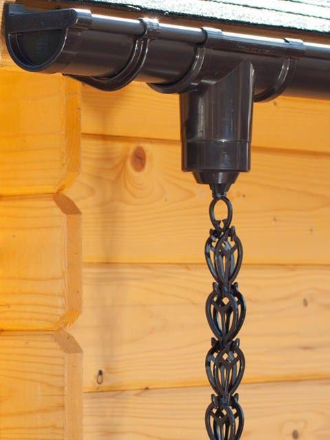 Bruine regenketting aan een dakgoot van een blokhut.
