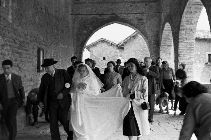 San Giorgio di Cascia, anni 50. Il porticato della hiesa parrocchiale, un anziano genitore accompaga la figlia all'altare, mentre una ragazza del paese, sostiene il velo nuziale della sposa. I bambini raccolgono i confetti sulle grandi pietre del porticato della chiesa.