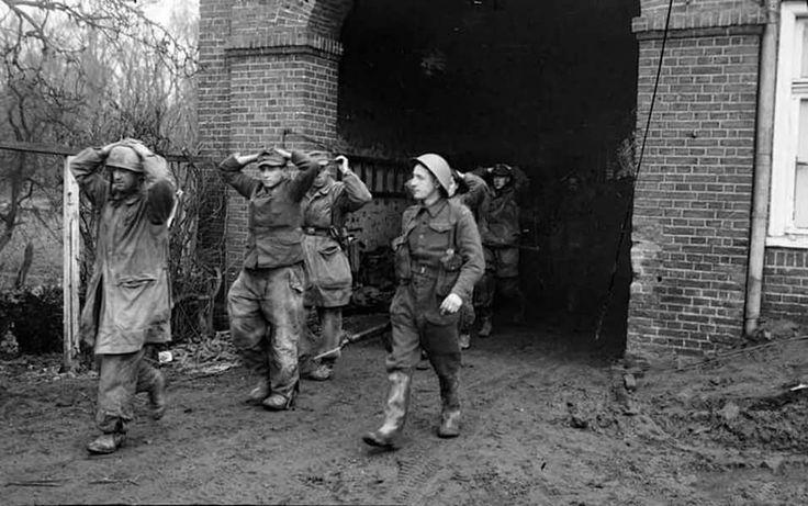 Un soldat canadien escorte des parachutistes allemands pris durant les combats près de Uedem, le 28 février 1945.