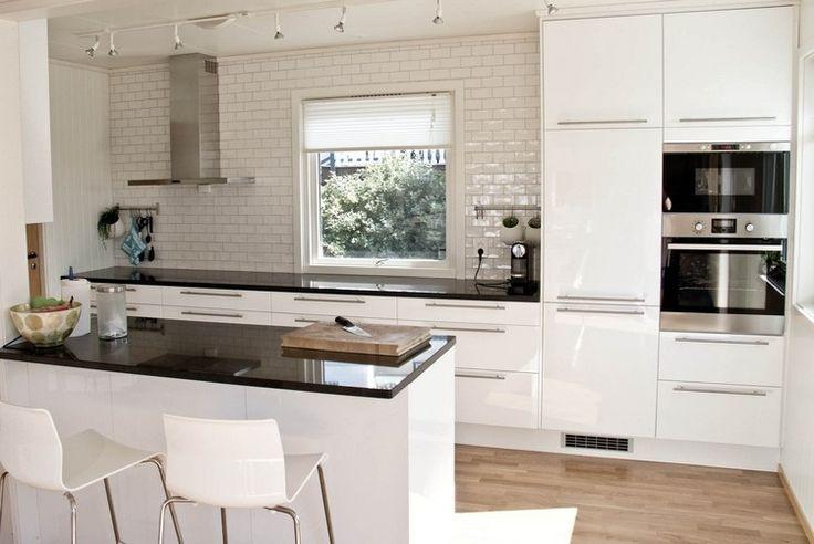cuisine blanche et moderne avec carrelage métro blanc et plan de travail noir