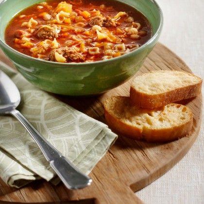 Kneed de helft van de kaas door het gehakt en vorm er kleine balletjes van. Verhit de olijfolie in een soeppan en bak hierin de spekblokjes, knoflook en ui 5 minuten. Voeg de tomatenpuree toe en bak deze even mee. Schep de wortel, kool en Italiaanse kruiden erdoor. Giet de bouillon erbij en roer de pasta en gehaktballetjes erdoor. Kook de soep met deksel op de pan zachtjes 20 minuten. Serveer de soep met ciabattabrood. Sprenkel er olijfolie over en bestrooi met de rest van de Parmezaanse…