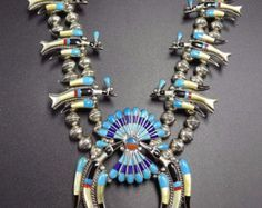 OLD NAVAJO SQUASH BLOSSOM NECKLACE DESCRIPTION: This exquisite squash blossom necklace dates from the 1930s to 1940s. It features 19 specimens of deep Blue Gem turquoise set in scalloped bezel. The sterling silver blossoms have a fleur-de-lis design, with loads of stamp-work and chiseled outline. Oversized hand-made beads complete the chef-douevre. This museum quality necklace will be a valuable addition to your collection of fine vintage Native American jewelry. MEASUREMENTS: Necklace ...