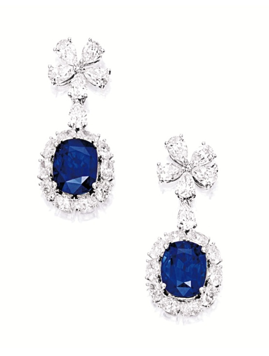 PAIR OF SAPPHIRE AND DIAMOND PENDENT EARRINGS. Each suspending on a cushion-shaped sapphire weighing 9.90 and 9.35 carats respectively, framed by oval diamonds, surmounted by a cluster of pear-shaped diamonds, the diamonds altogether weighing approximately 9.90 carats, mounted in 18 karat white gold.