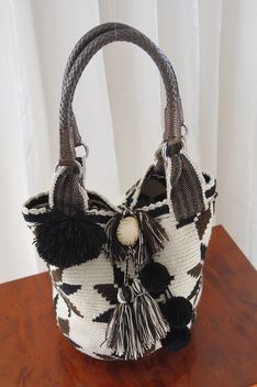 Mochila with leather straps - If you're looking for something that no one else has, this authentic mochila is it.  With its neutral color palette, braided leather handles and tagua loop closure, this bag is wearable all year round.  Aunthentic mochilas are made by the women of the Wayuu tribe, which is an Amerindian ethnic group of the La Guajira Peninsula in northern Colombia and northwest Venezuela. $285