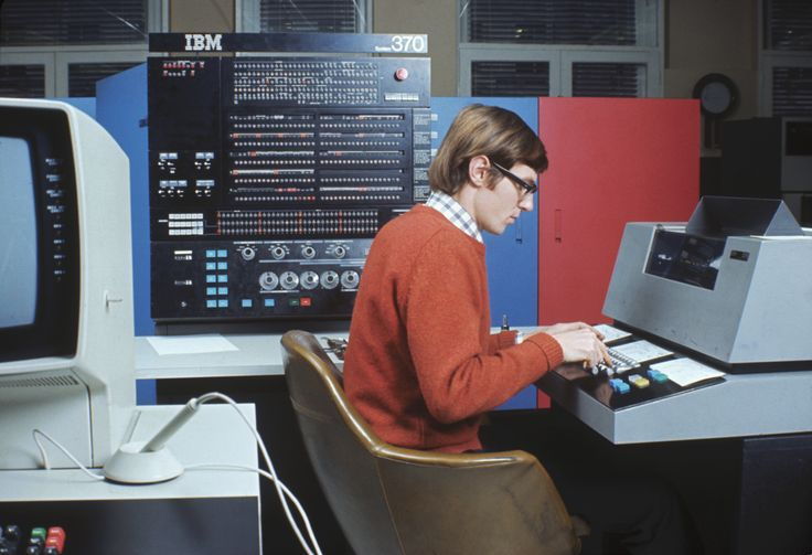 A man sits at an IBM System/370 mainframe computer in this 1970 photo. The S/370 is notable as one of the first computers to include full support for virtual memory.