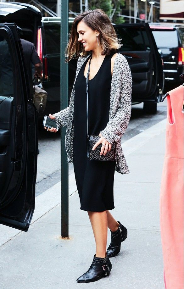 Jessica Alba wears a black tank dress, gray sweater, black studded booties, and a mini black crossbody bag