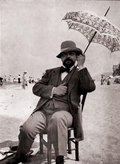 Claude Debussy, brilliant composer, even more brilliant umbrella fashionista and beach patron.