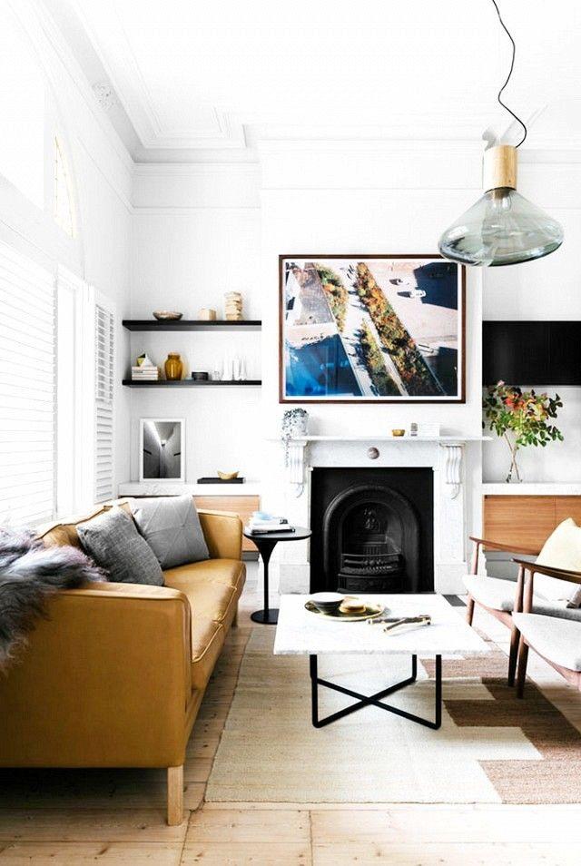 Scandinavian inspired living room with black cabinets,  reclaimed wood floors, and a camel leather sofa