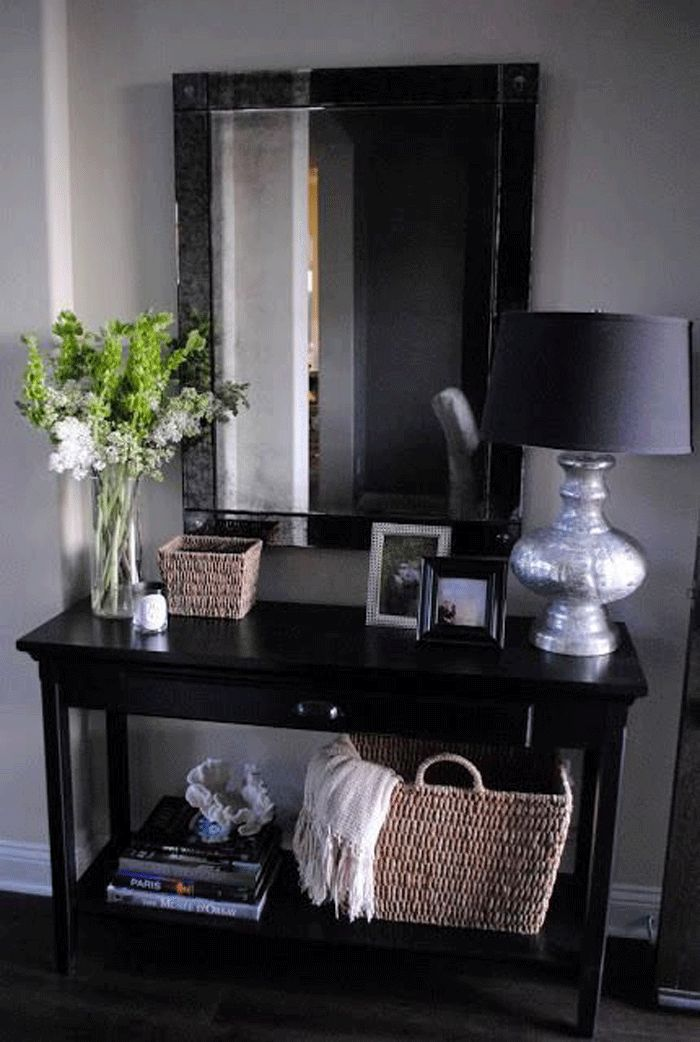 Foyer. Would need to go a little smaller and a little less clutter but could use mirror and bold lamp.