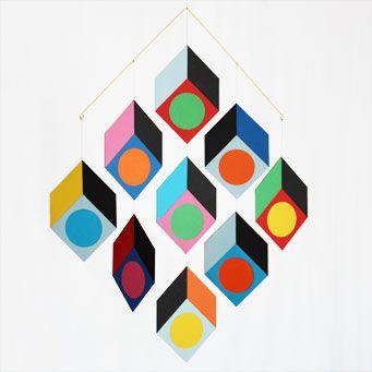 Dekorativ uro i mange farver fra fynske Livingly. Cubillusion er en hyldest til 1960′ernes Op art, som eksperimenterede med optiske virkemidler. Selvom elementerne i denne uro er flade, snydes øjet til at se enten det indvendige eller udvendige af rumlige kubiske former.  Uroen er lavet af papir af hjemmearbejdere på Fyn. #opart#klassisk#uro#mobile#livingly#designbutik