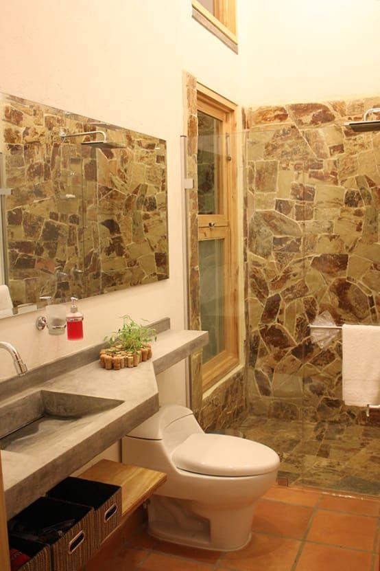 Baño con pared de piedra por interior137 arquitectos