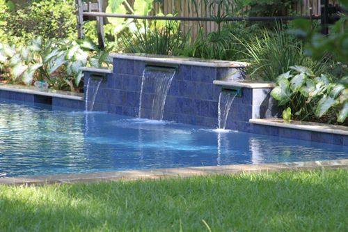 Swimming pool raised wall with water features in mt for Raised swimming pool designs