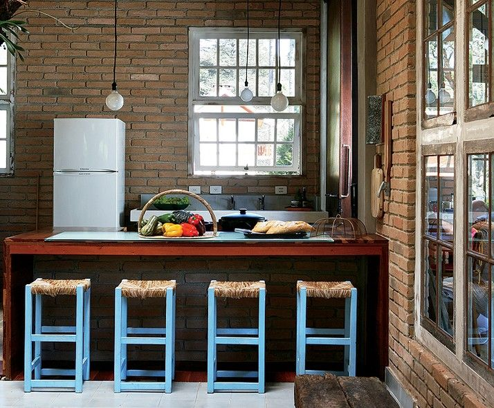 A cozinha segue o estilo simples da casa de campo da arquiteta Evelin Sayar. A iluminação é feita por lâmpadas penduradas e as banquetas de fibra dão um toque de cor
