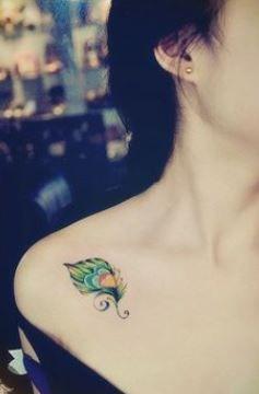 Piccola piuma di pavone colorata tatuata sulla spalla
