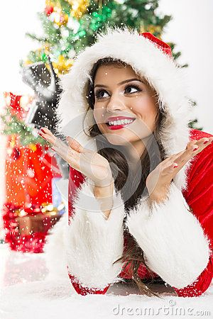 Cute young smiling woman wearing a Christmas costume enjoying the falling snow while lying on the ground.