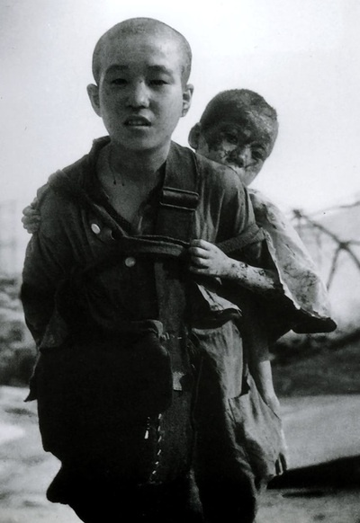 A boy carries his brother, covered with burns from the atomic bombing of Nagasaki. August 10, 1945.   Yōsuke Yamahata