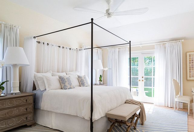 Master Bedroom. Coastal master bedroom. Master bedroom with oversized fan and iron canopy bed. White cotton linens, blue and white wool rug, linen upholstered bench and sheer drapery. Nightstands are substituted by large chests with oversized lamps which work well with the oversized scale of the bed and drapery. #masterbedroom #CoastalBedroom #CoastalMasterBedroom Chango & Co.