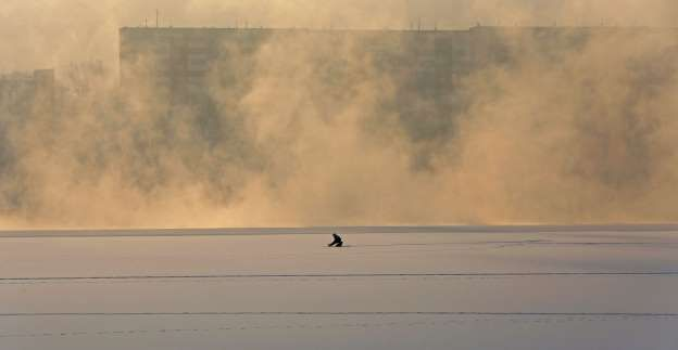 A man fishes on an ice-covered section of the Yenisei River, with the air temperature at about minus 20 degrees Celsius (minus 4 degrees Fahrenheit), in the Siberian city of Krasnoyarsk, Russia on Nov. 21, 2015.