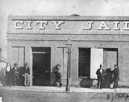 """Denver Jail in 1874 A group of men stand outside the Denver City Jail located at 231 Thirteenth (13th) Street, Denver, Colorado. A police officer stands outside a set of large wooden doors. The building is a one story brick structure with heavy wood shutters. Bars cover the windows. Large letters painted on the front of the building read: """"City Jail."""" :: Western History"""
