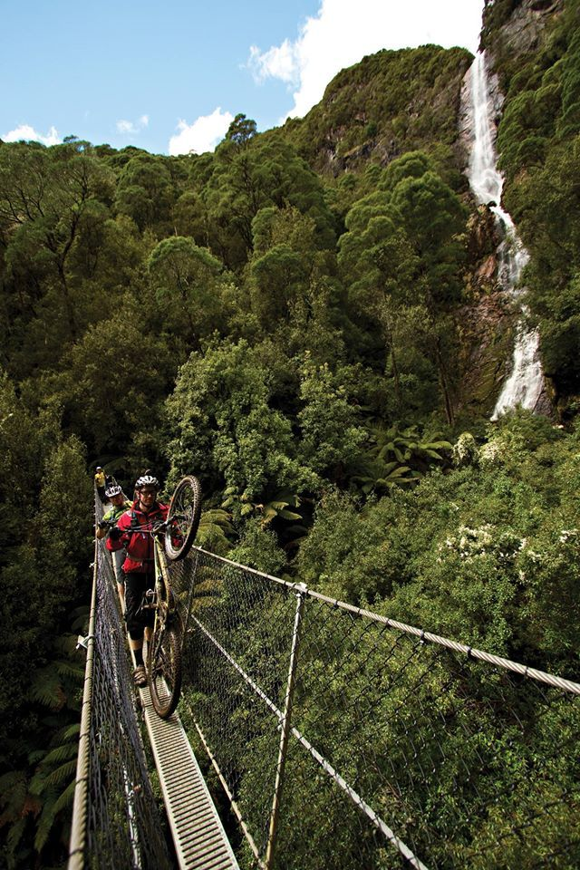Crossing the swing bridge at Montezuma Falls, near Rosebery on Tasmania's west coast. / Image Credit: Vertigo Mountain Biking