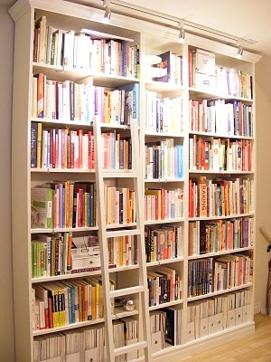 Billy bookcase from Ikea with crown molding... I love the lighting and the library ladder