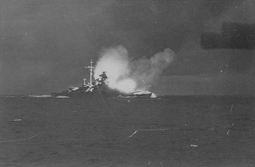 """The Bismarck in Battle    The Bismarck in Battle. This photo is the most well known of the battleship Bismarck and one the most famous of World War II as well. It was taken from the Prinz Eugen sometime between 0607 and 0609 hours on 24 May 1941. By then the Hood had already been sunk and the Bismarck hit on her bows. The after turrets """"Cдsar"""" and """"Dora"""" are firing against the Prince of Wales in one of the last salvoes of the battle."""