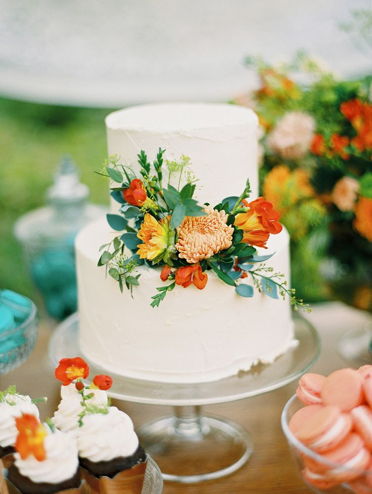 Simple white cake decorated with fresh flowers from the season. Rustic wedding cake.