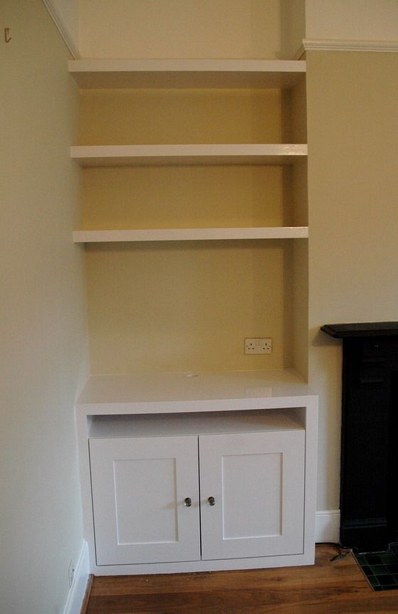 Cabinet includes open shelf for sky box; floating shelves above