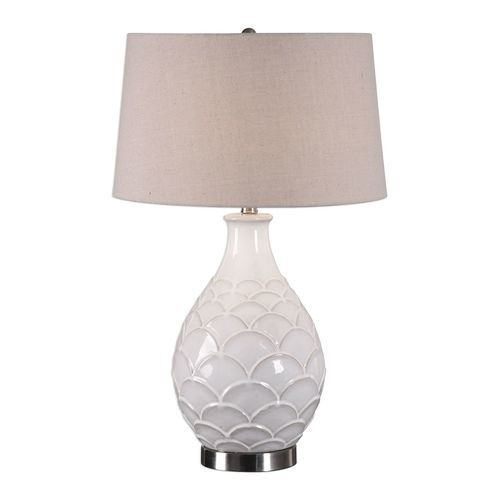 The slightly distressed off-white glossed ceramic base of this Camellia Table Lamp is accented with scale-like texture and polished nickel plated details.