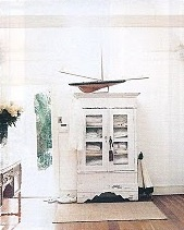 A model yacht sits on an antique armoire in the garden cottage