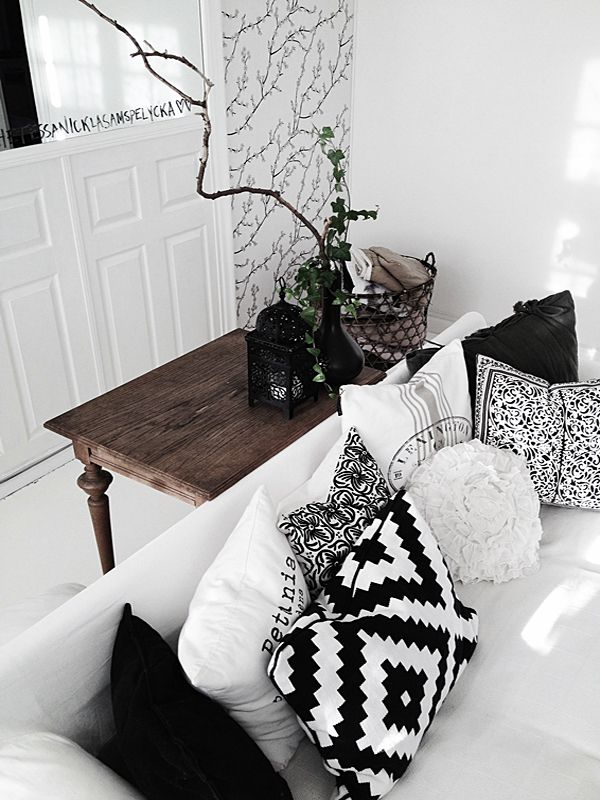 White living room, black patterned pillows, marble, White couch, wood side table warms it all up