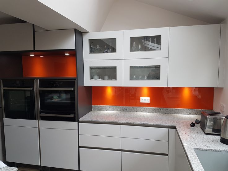 Orange glass painted splashback adding vibrancy to this kitchen.