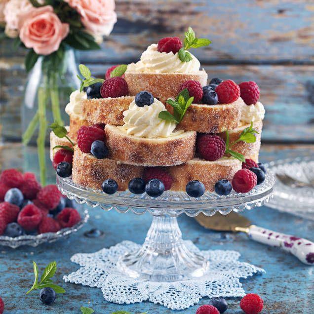 Det är festligt att göra en tårta av rulltårtan skuren i skivor och garnera med vispad grädde och färska bär.