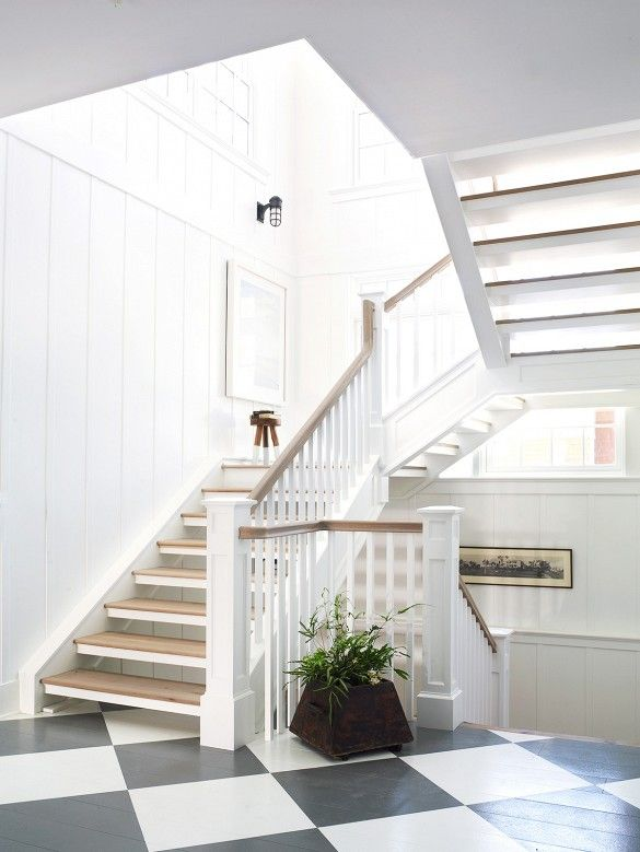 Black and white grid flooring and wooden and white staircase.