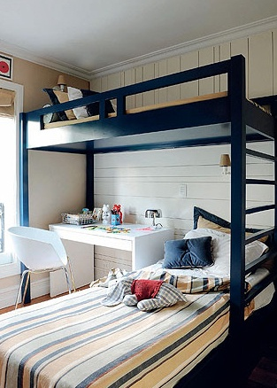 O dono deste quarto dorme sozinho, mas tem um lugarzinho extra para receber os amigos. Mesa e cadeira couberam no vão ao lado da cama inferior