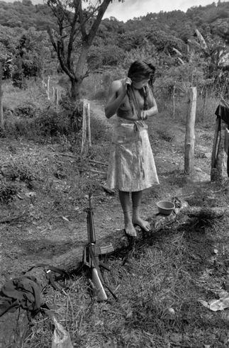 Bañandose pero siempre alerta...Mujer guerrillera en El Salvador