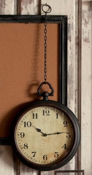 "Lovely timeless look with this pocket watch wall clock accented by distressed black paint metal frame and 18"" chain. Measures: 21"" x 17"" x 18"""