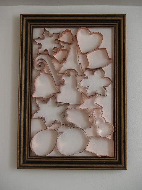 Copper cookie cutters in a thrift store frame
