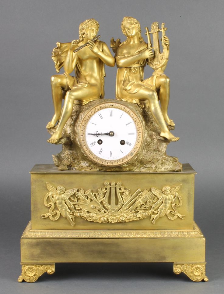 LOT 793, A 19th Century French 8 day striking mantel clock with paper dial and Roman numerals, contained in a gilt ormolu case surmounted by 2 figures of male and female classical musicians SOLD £340